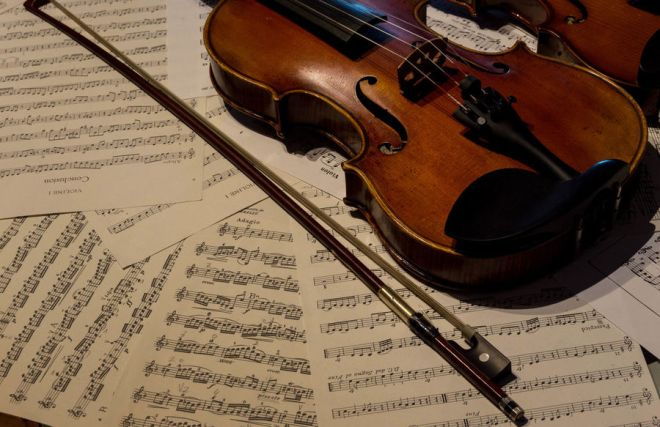 Wooden violin on a sheet music.